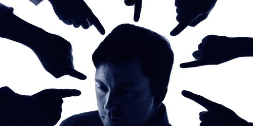 People pointing at businessman, close-up (blue tone, grainy)